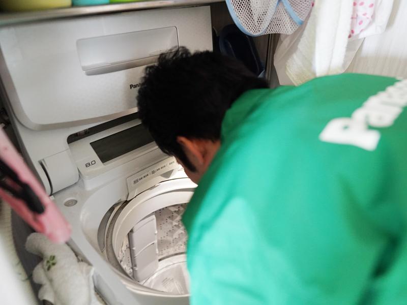洗濯機の点検をするスタッフ